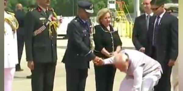 PM bends to pick up flower that fell from bouquet presented to him