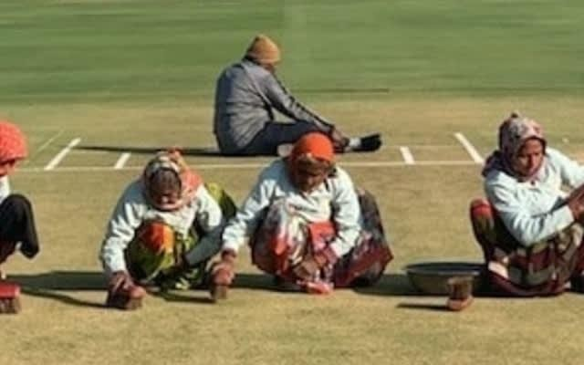 4 elderly women scrub grass clippings off the pitch ahead of Rajkot ODI